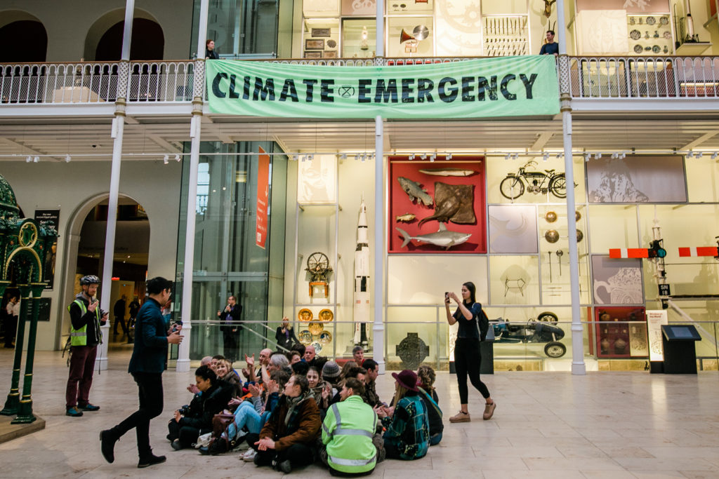 Protesters sit on floor in middle of museum as other protesters hang flag from balcony saying Climate Emergency