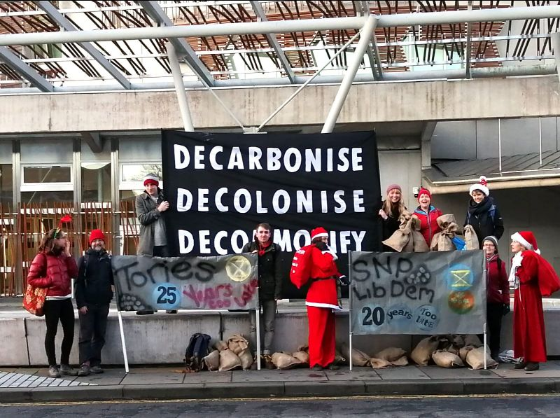 Rebels stand in front of a banner saying Decarbonise, Decolonise, Decomodify