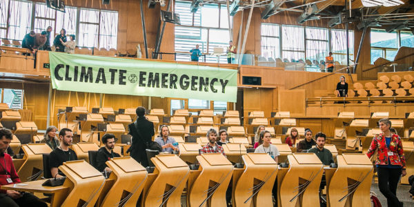 XR Scotland protestors in Scottish Parliament hanging up banner saying Climate Emergency