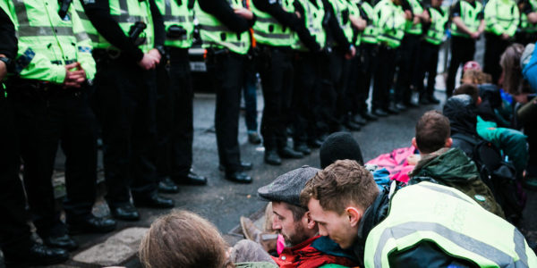 Line of police stand next to row of Extintion Rebellion protesters sitting on ground.