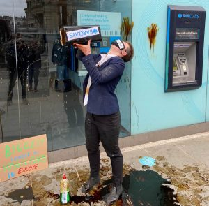 Climate activists stage performance outside a Barcalays bank. Person dressed as Barclays worker about to pour oil on themselves.