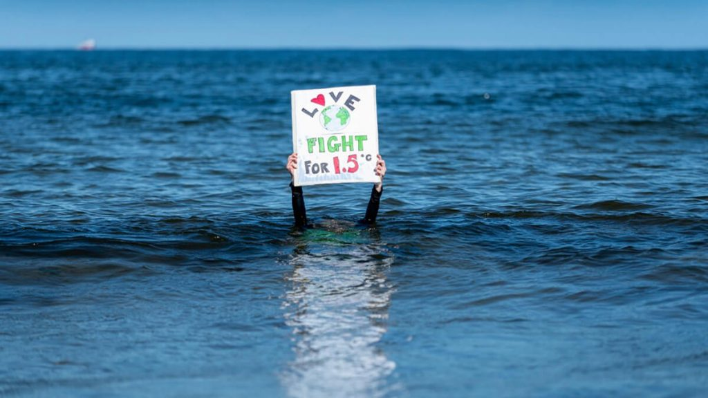 XR Forres - climate activist underwater holding up sign saying 'love earth fight for 1.5 degrees'