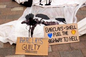 Climate activists shrouded as 'Dead bodies' covered in oil outside a Barcalays bank, Glasgow. Signs say 'Barclays Guilty' and 'Barclays + 'Shell fuel the highway to hell'.