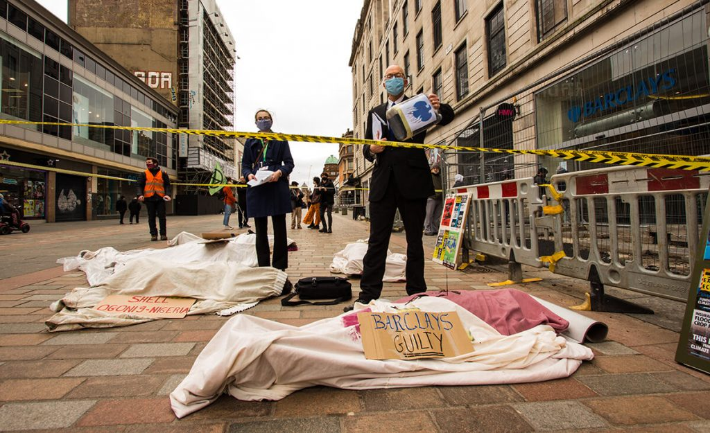 Climate activists stage performance outside a Barcalays bank, Glasgow using 'dead bodies' covered in oil. Sign say 'Barclays Guilty'.