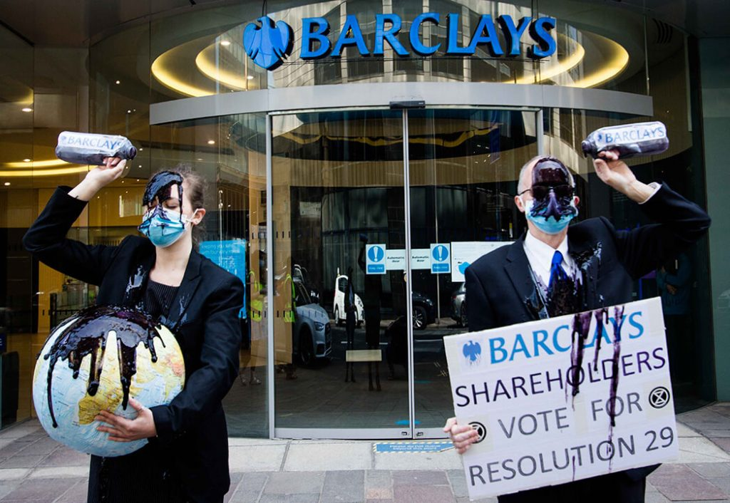 Climate activists in suits pour oil over themselves outside a Barcalays bank
