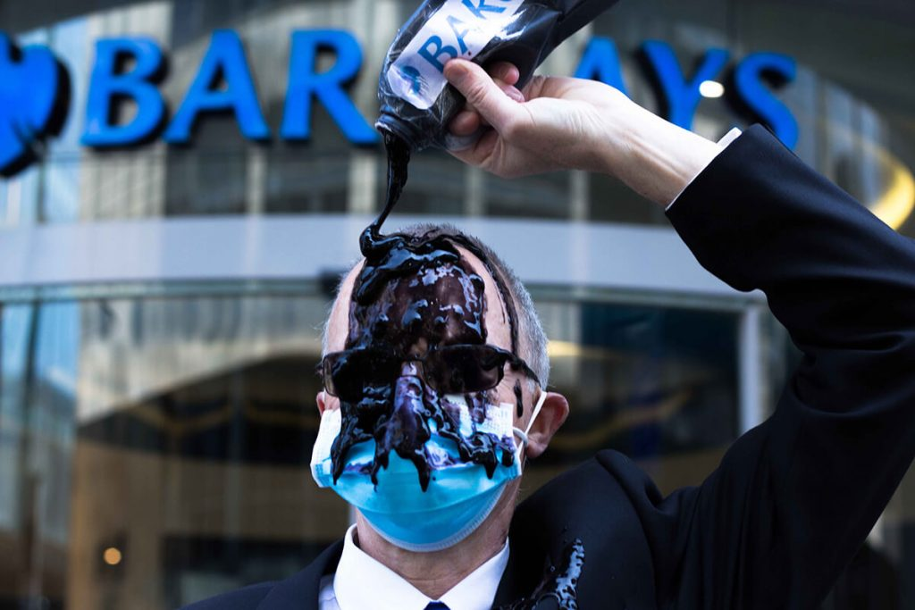 XR Scotland activist Climate activist in suit pours oil over themselves outside a Barcalays bank