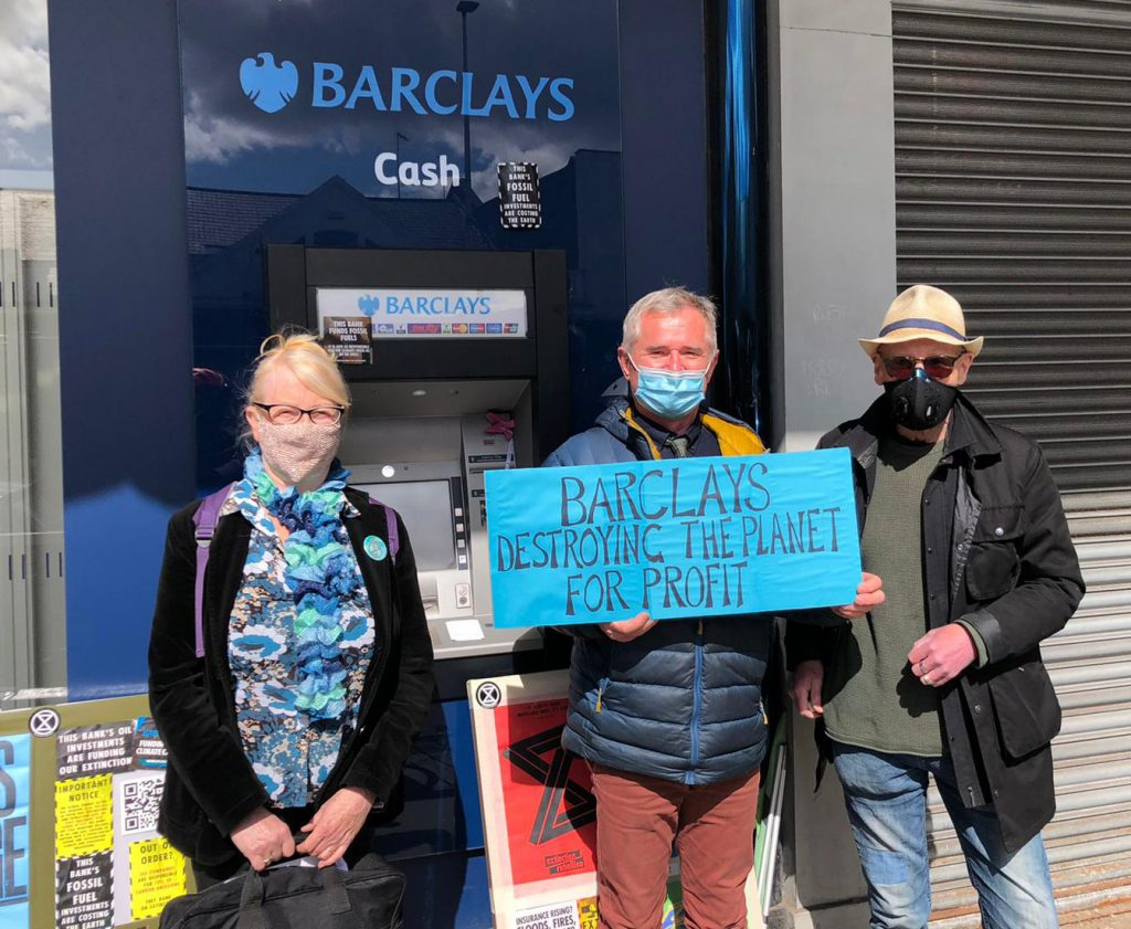 Three Extinction Rebellion Glasgow activists protest outside a Barclays branch