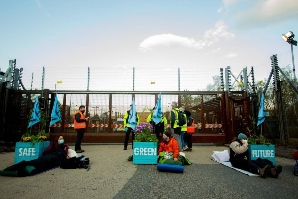 Three Extinction Rebellion Scotland activists locked to flower planters saying Safe, Green Future on them. Actvisists are in front of main gate to Faslane.