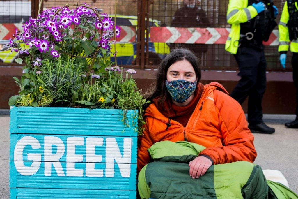 Activist locked to flower planter with 'Green' painted on it.