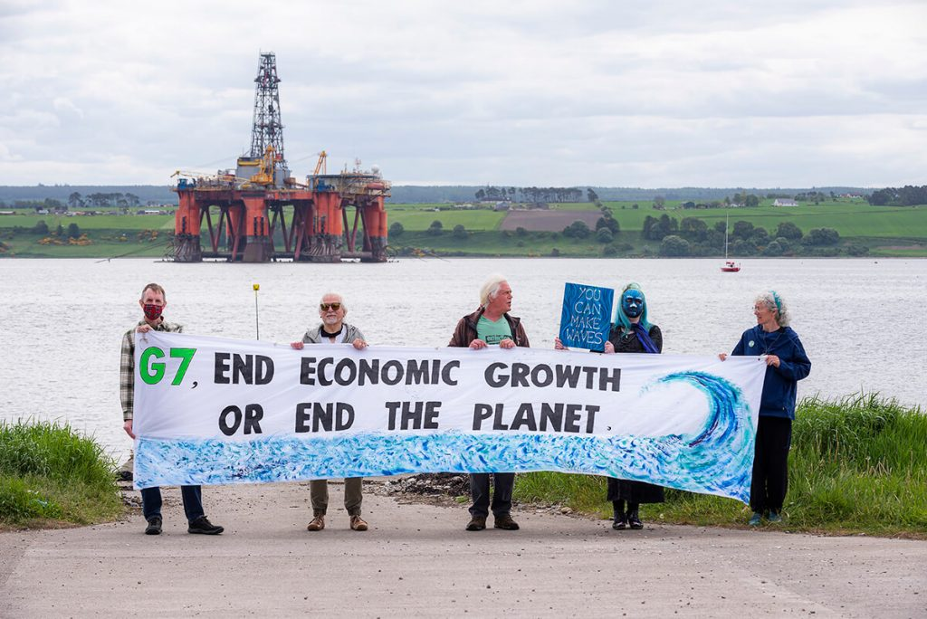 XR Inverness activists hold banner saying 'G7: End Economic Growth or End the Planet' in front of North Sea oil rig