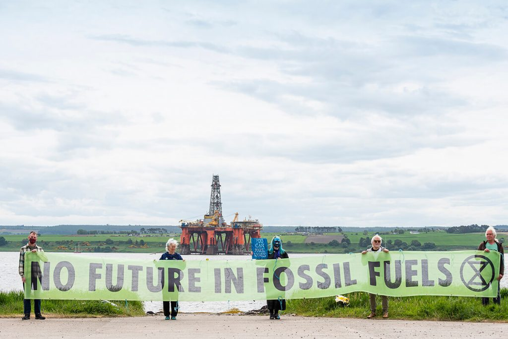 XR Inverness activists hold banner saying 'No Future in Fossil Fuels' in front of North Sea oil rig