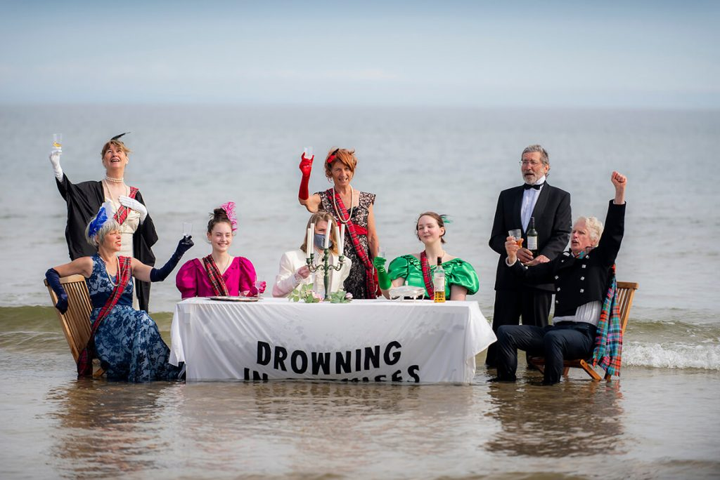 Rising sea engulfs Edwardian tea party on the beach. Banner says Drowning in Promises.