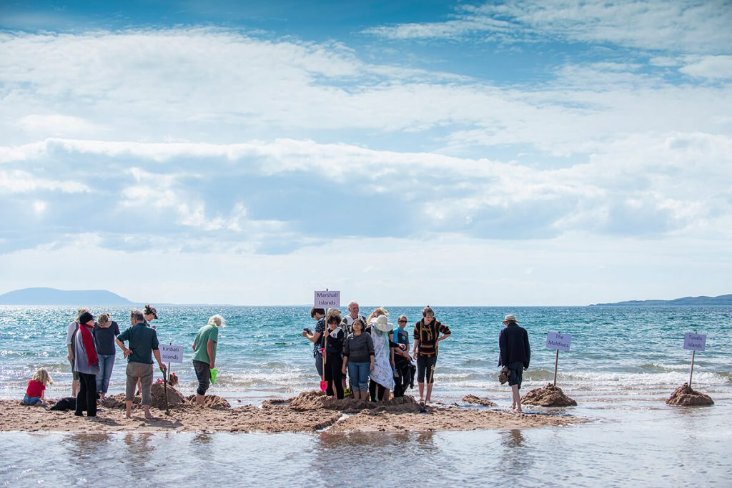 Activists stand on sand bank surrounded by sea to show affect of rising levels on small islands