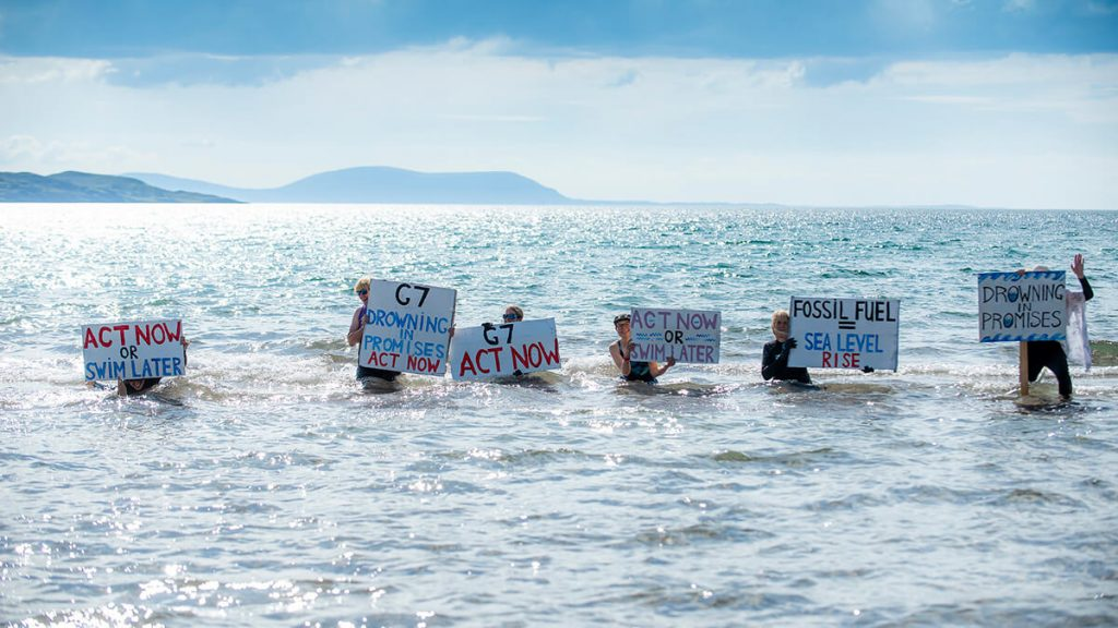 Activists standing in sea with placards saying 'Act Now or Swim Later' or 'Fossil Fuel = Sea Level Rise'