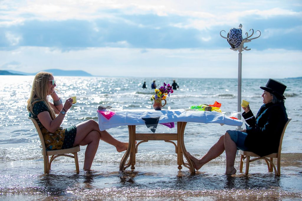 Two climate activists sit having a drink at a table in the sea
