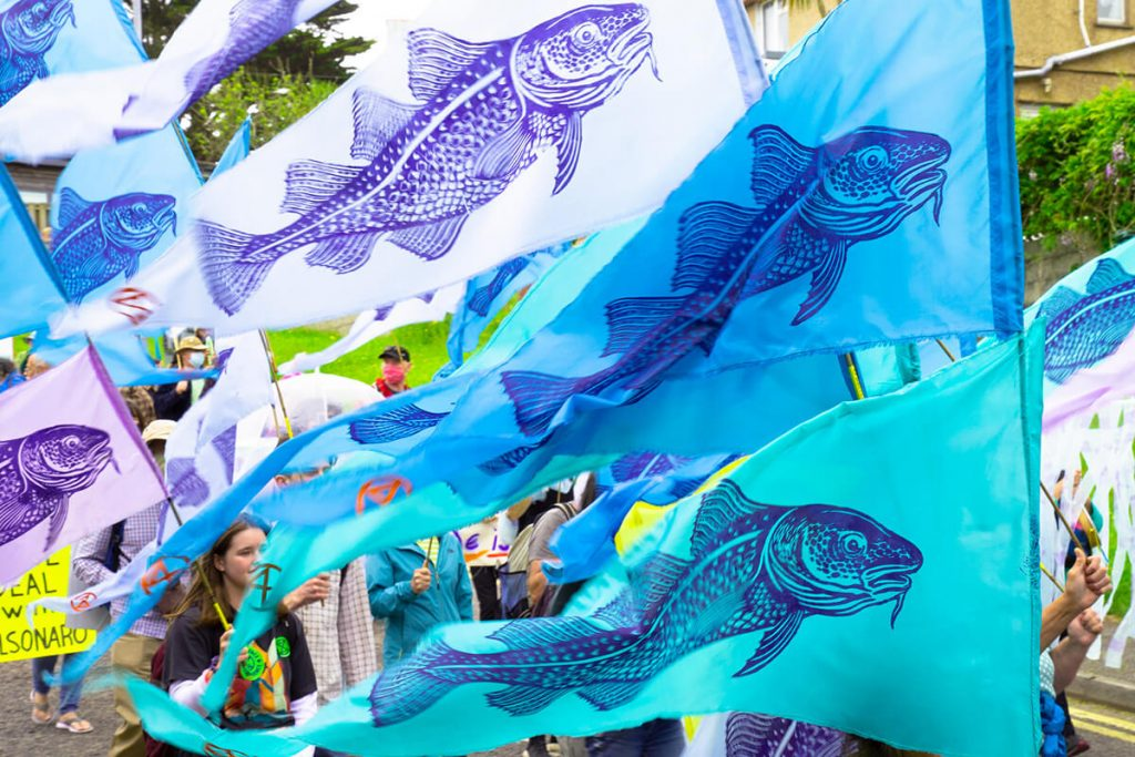 Colourful flags with fish stencilled on being carried by climate marchers