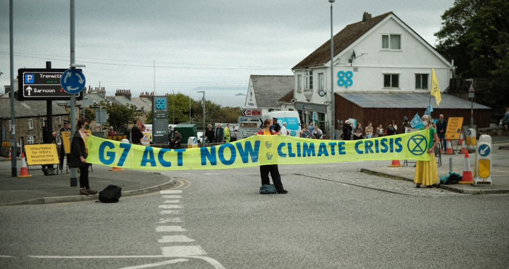 Climate activists hold a banner across a road
