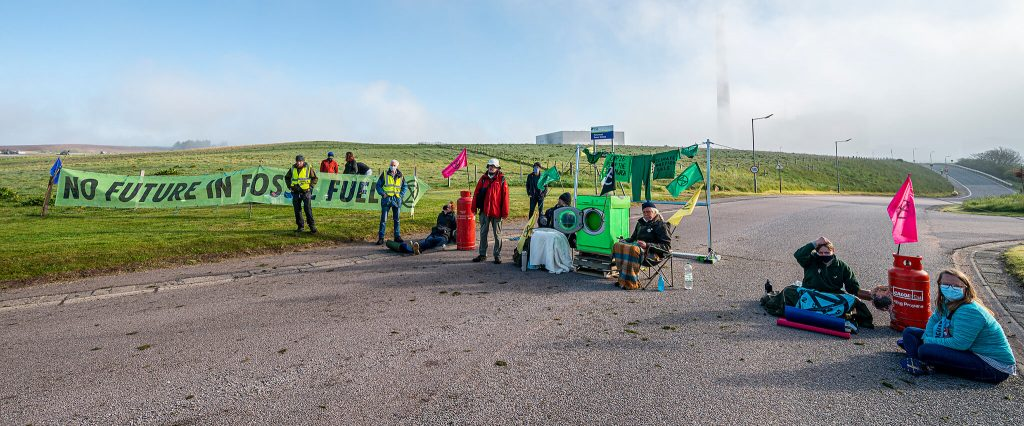 Peterhead Power Station: activists block road with banners, gas canisters and washing machine. Peterhead Power Station chimney in background shrouded by fog.