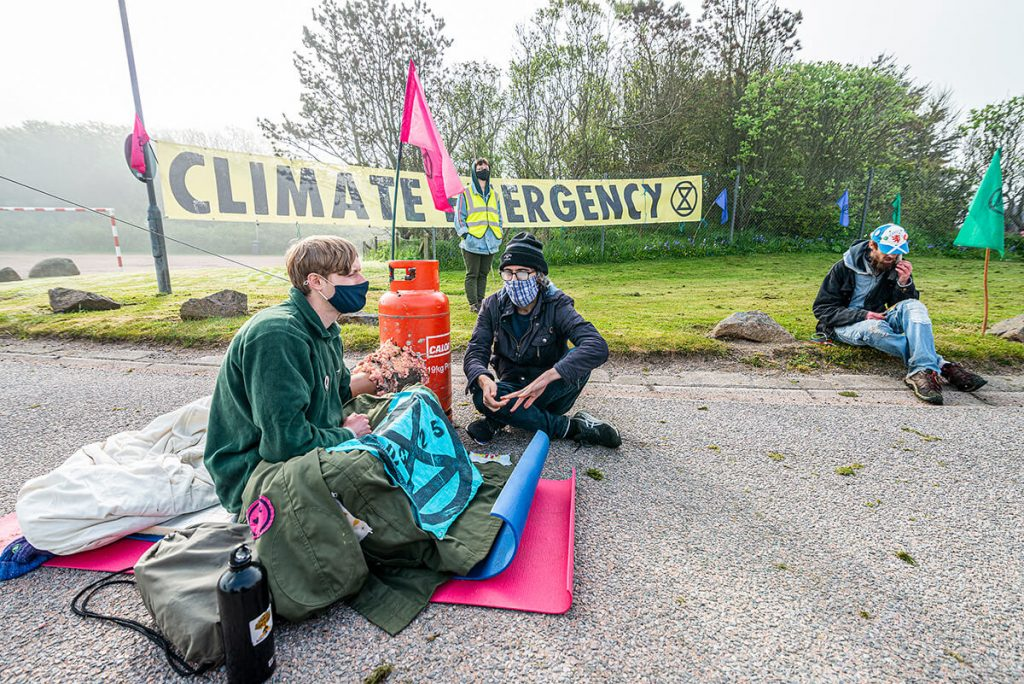 Peterhead Power Station: activist sitting on road and locked on to gas canister