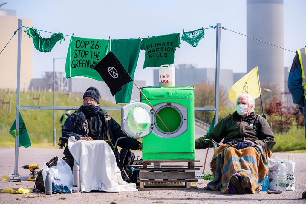 Activists sitting and locked onto green washing machine with Peterhead Power Station in background.