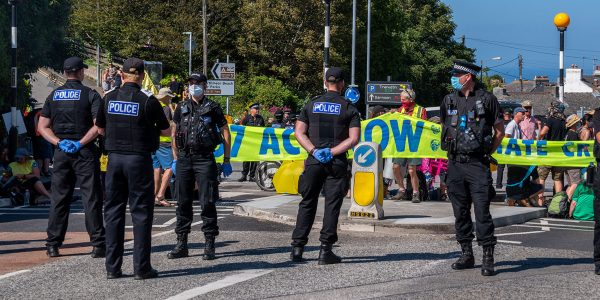 Protestors behind a line of police block a road at G7