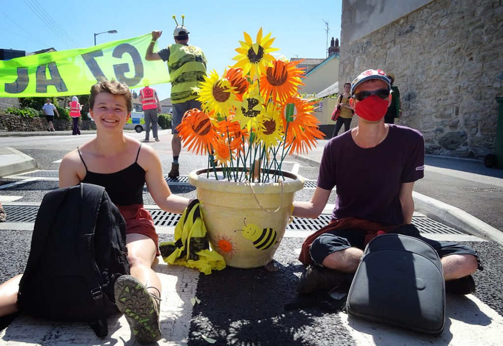 Two people sitting on road locked onto pot with colourful artificial flowers.