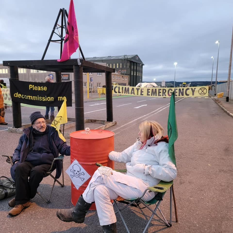 Two activists locked to oil barrel in front of model oil rig saying 'Decommission Me' on it